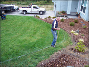 Using a tool to cut the sod into smaller pieces for removal.